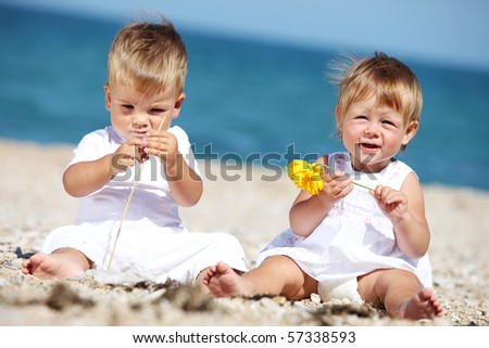 Little boy and girl playing by the sea in summer