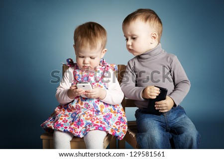little boy and girl playing with mobile phones