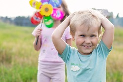 little boy and girl playing with windmill in the fresh air with copy space
