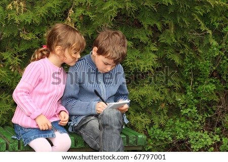 little boy and girl sitting on bench near trees, boy writing in notebook, girl looking on it