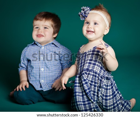Little boy and girl smiling sitting together