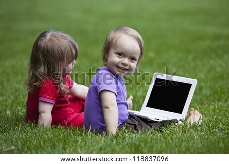 Little boy and girl using a little Laptop while sitting on meadow. The black space on the laptop could be used for any logos, some label signs or any graphic additions.