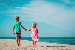 little boy and girl walking on beach
