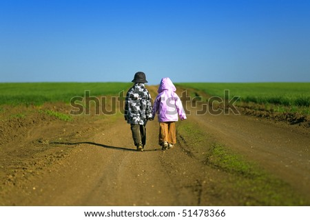 Little boy and girl walking through field a bright spring's day