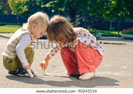 little boy and girl with crayons, they drawing on the asphalt