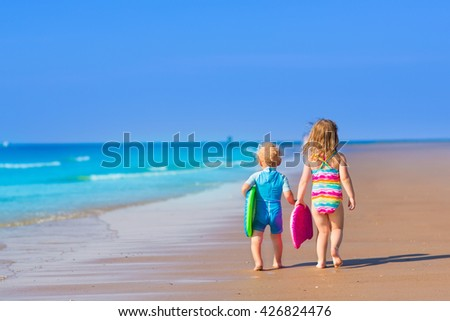 Little boy and girl with surfing boards playing on tropical ocean beach. UV and sun protection for young children. Summer water fun for surfer kids. Child learning to swim and surf with body board.
