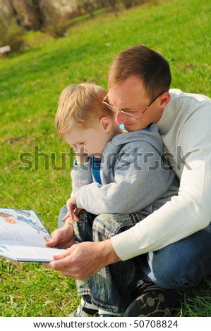 Little boy and his father are reading a book outdoor