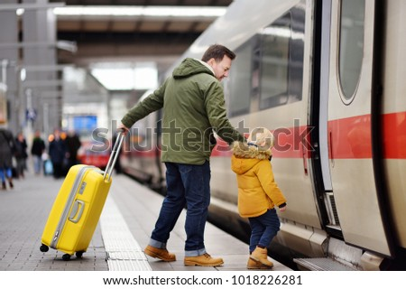 Little boy and his father go in express train on railway station platform. Travel, tourism, winter vacation and family concept. Man and his son together.