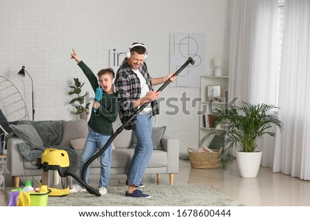 Little boy and his father having fun while hoovering floor in room Photo stock ©