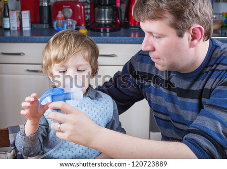 Little boy and his father making inhalation with nebuliser, inhalator in home kitchen