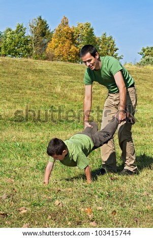 Little boy and his  father playing outside