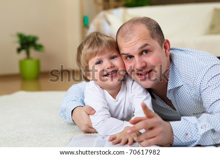 little boy and his father playing together at home on the floor #70617982