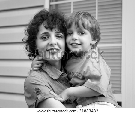 Little boy and his mother in front of house in B&W