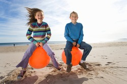 Little boy and his sister sitting on inflatable hoppers and bouncing on the beach on a bright, sunny day