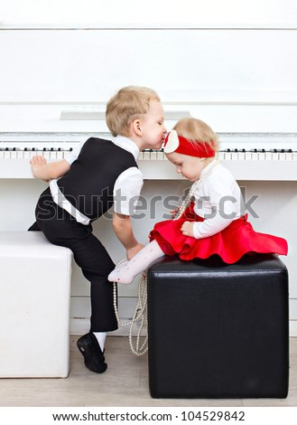 little boy and little girl near the white piano - stock photo