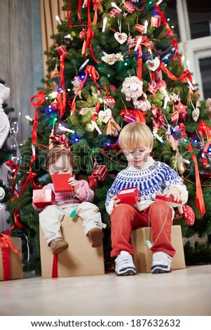 Little boy and little girl sit on big cardboard gift boxes under Christmas tree, holding open gift boxes of smaller size