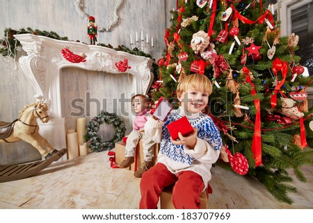 Little boy and little girl sit on big gift boxes under Christmas tree, holding open gift boxes of smaller size