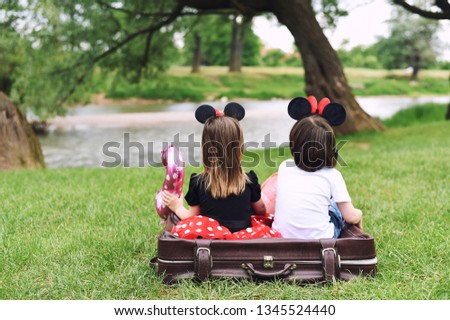 Little boy and little girl sitting in a suitcase next to the river