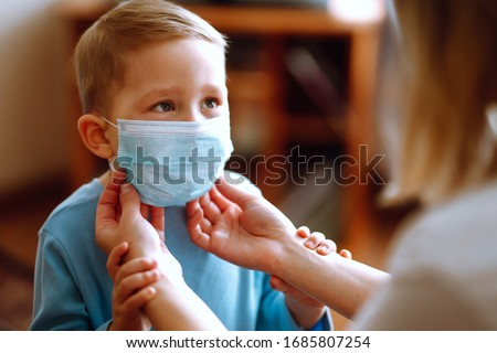 Little boy and mom in medical mask. Mother puts on her baby sterile medical mask. Child, wearing face mask, protect from infection of virus, pandemic, outbreak and epidemic of disease on quarantine. Foto stock ©