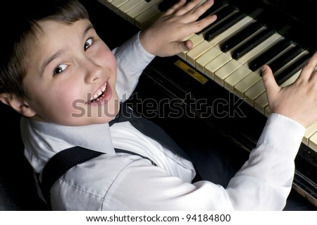 Little boy and piano. - stock photo
