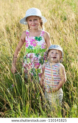 Little boy and pretty girl in a field of grass
