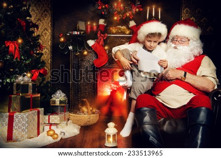 Little boy and Santa Claus reading letters from children. They are at home, decorated for Christmas. Santa\'s mail.