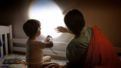 Little boy and young mother showing shadow theater on wall in bedroom at night.
