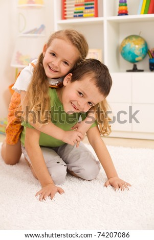 Little boy anf girl wrestling and having fun in their room