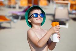 Little boy applying sunscreen spray on beach
