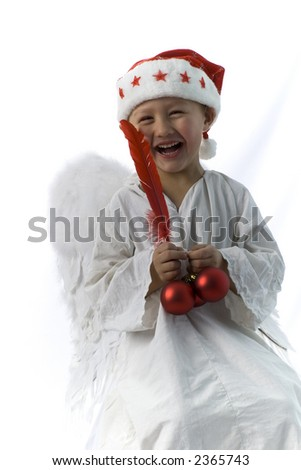 little boy as angel in red xmas hat ,ball and feather