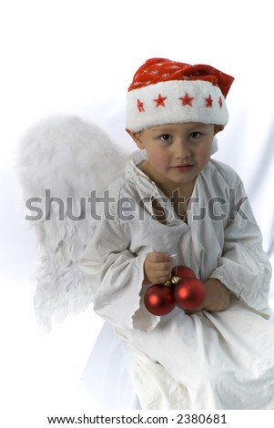 little boy as angel in red xmas hat with ball