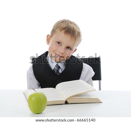 little boy at his desk with books and apple. Isolated on white background