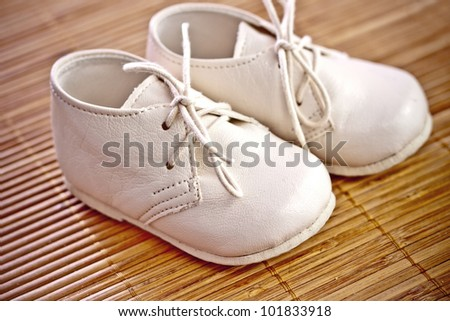 little boy baby shoes on a wooden floor