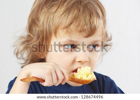 Little boy bites millet porridge from a wooden spoon