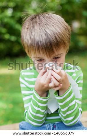 Little boy blowing his nose because of allergy in the garden