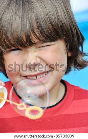 Little boy blowing soap bubbles - stock photo