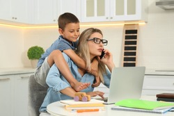 Little boy bothering mother at work in kitchen. Home office concept