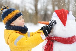 Little boy building funny snowman. ?hild attaches carrot nose to snowman in snowy park. Active outdoors leisure for children and family in winter