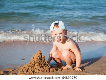 little boy builds a sand house on a beach