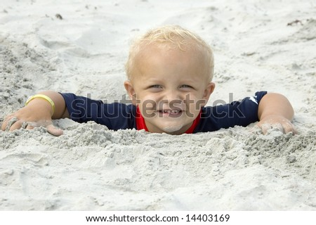 Little Boy Buried in Sand up to Head