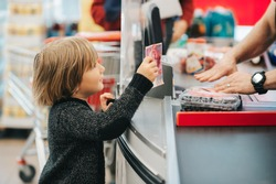 Little boy buying fruits in a food store, holding 20 chf bill