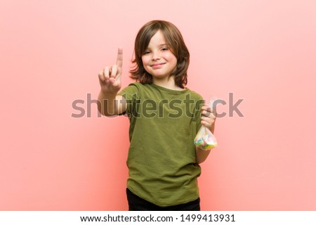Little boy caucasian holding candies showing number one with finger. #1499413931