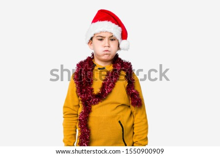 Little boy celebrating christmas day wearing a santa hat isolated blows cheeks, has tired expression. Facial expression concept.