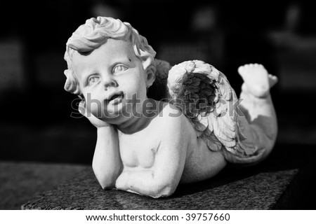 Little boy cherub with wings laying down with his head in his hands.