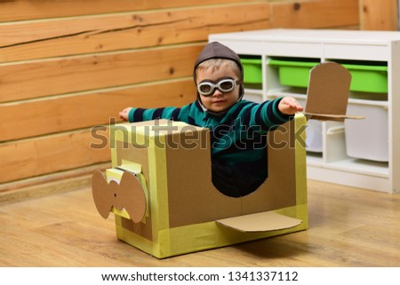 Little boy child play in cardboard plane, childhood. Kid, pilot school, innovation. Dream, career, adventure, education. Air mail delivery, aircraft construction Pilot travel airdrome imagination