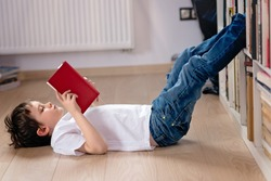 Little boy child reading a book in the library. He lies on the floor. Legs on bookshelf
