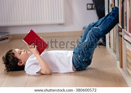 Little boy child reading a book in the library. He lies on the floor. Legs on bookshelf #380600572