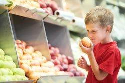 Little boy choosing bio apple food in fruit vegetable shopping store