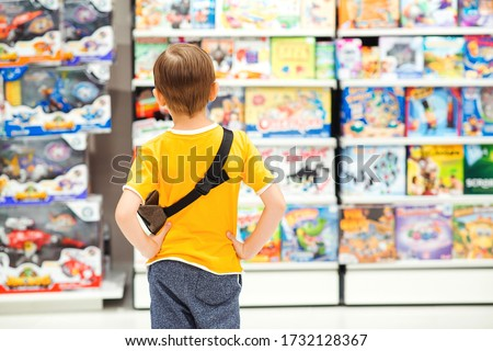 Little boy choosing toys for birthday gift. Many toys around. Kids shop. Sales, discounts and shopping. Cute boy selecting toys in store. Child doing shopping in toys shop.