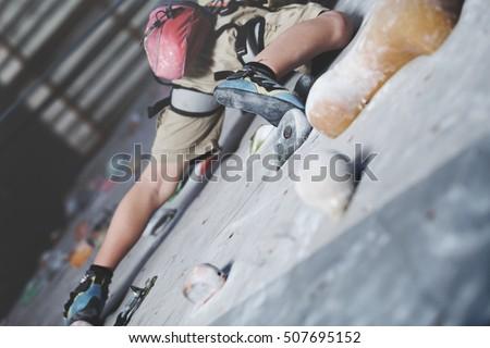 little boy climbing a rock wall indoor #507695152